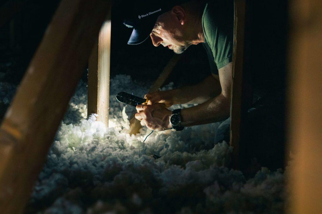 homme isolant le plafond d'une maison